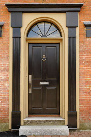 front door: An elegant brown door with brass accents in a brick building. Vertical shot. Stock Photo