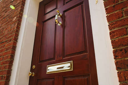 Low angle view of an elegant red door with brass accents in a brick building. Horizontal shot.