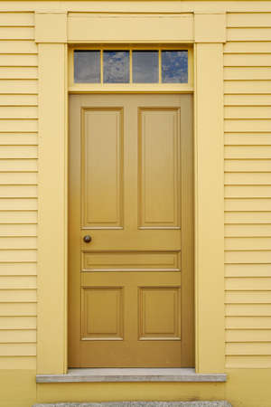 An unadorned yellow door set in to the facade of a wooden building. Vertical shot. Stock Photo - 7098948