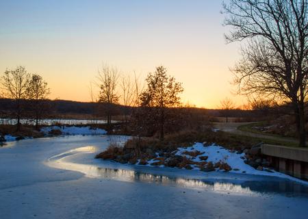 frozen lake: frozen lake along walking path at sunset in winter
