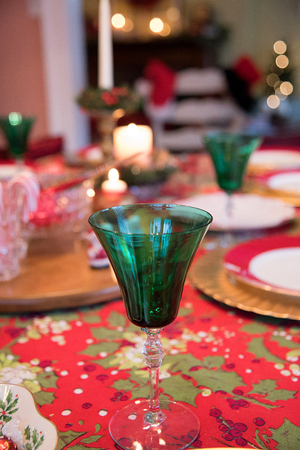 closeup soft focus view of Christmas dinner table with gold chargers and green glasses Stock Photo