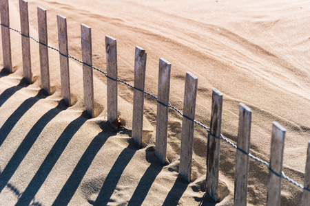 weathered wood protective fence along sand dunes with long afternoon shadows