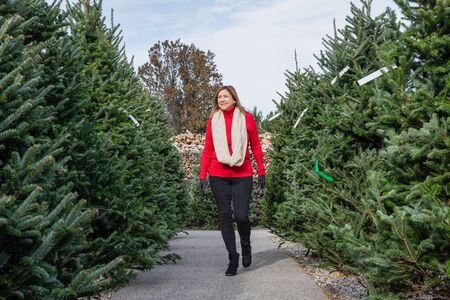 smiling middle age woman looking for a fresh cut Christmas tree outside at garden center