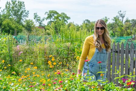 stylish young woman in denim overalls smiling and walking through community garden in summer Imagens