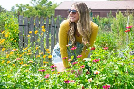 happy young woman working in garden in summer wearing jean overalls