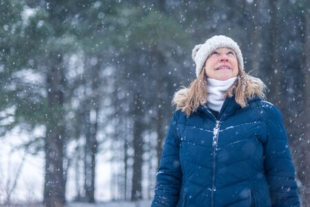 smiling middle age woman looking up at snowflakes falling in forest on hiking trail in winter