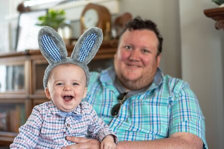 cute little boy wearing rabbit ears sitting on dads lap at home on Easter morning