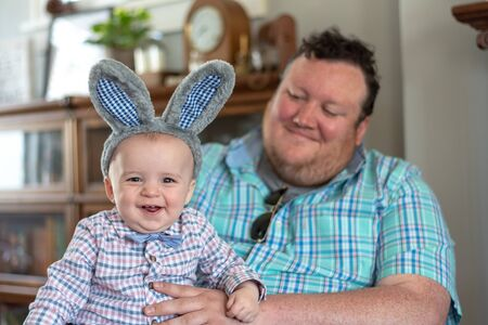 Boy wearing Easter outfit sitting on dads lap at home visiting with family Stock fotó