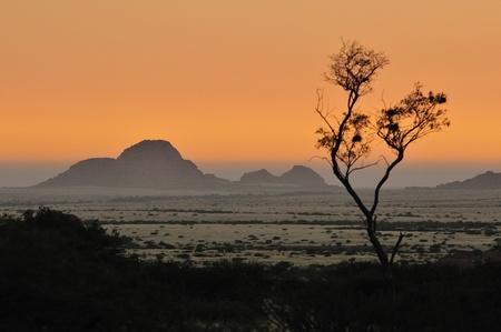 バック グラウンドで小さなスピツコッペとスピツコッペ、ナミビアからの夕日 写真素材