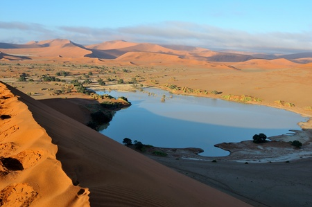 A rare sight: Sossusvlei in the Namib desert of Namibia filled with water. Some of the highest dunes in the world are in the background. Stock Photo