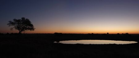 Panorama from two photos  Sunset view of the waterhole, Okaukeujo Rest Camp,  Etosha National Park, Namibia