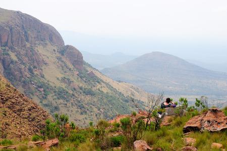 マラケレ、南アフリカ - 2011 年 12 月 2011 年 12 月 8 日撮影したマラケレ国立公園写真で山視点で景色を楽しみながらベンチに正体不明の人