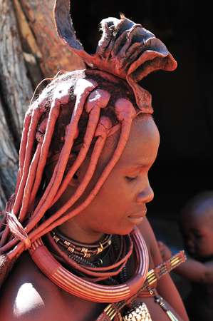 EPUPA, NAMIBIA - MAY 2011: An unknown Himba woman, with body colored in red ochre, poses for photographers at a Himba village on May 27th, 2011. Entrance fee to the village is a specified food parcel Editorial