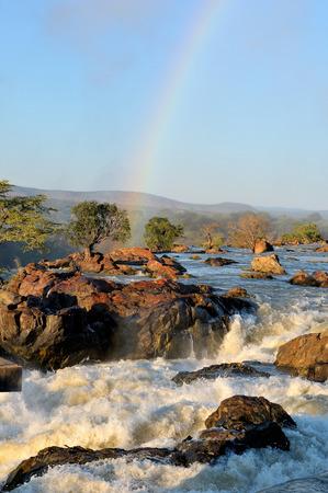 日の出のナミビアとアンゴラの国境にルアカナ滝の上部 写真素材