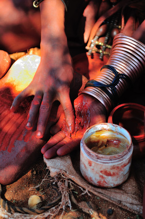 Himba woman mixing red ochre with petroleum jelly to apply to body  Traditionally it was mixed with animal fat