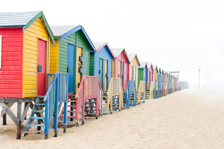 huts: Multi-colored beach huts disappearing in the mist at Muizenberg in Cape Town, Western Cape Province of South Africa Stock Photo