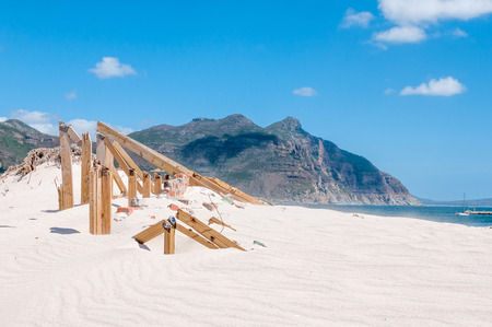 swept: Old police station at Hout Bay reclaimed by sand dunes, Cape Town, South Africa. Sand grains swept into the air is visible over the sea