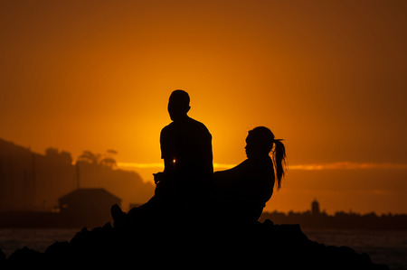 Silhouette of man and women against sunset over Gordons Bay in the Western Cape Province of South Africa Stock Photo