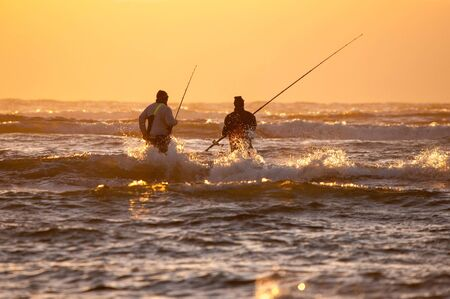 cape town: CAPE TOWN, SOUTH AFRICA - DECEMBER 20TH, 2014: Silhouette of two anglers against sunset at The Strand near Cape Town in the Western Cape Province of South Africa Editorial
