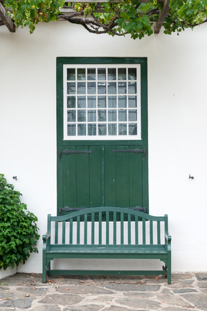 barn doors: Bench and window with barn doors at the Drosdy, a historic building in Swellendam in the Western Cape Province of South Africa Stock Photo