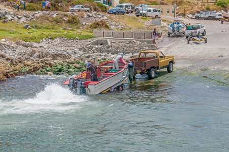 lobster boat: KLEINMOND, SOUTH AFRICA - DECEMBER 23, 2014: Crayfish boat being pulled with the days catch onto a trailer at Kleinmond harbor