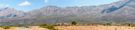 gat: SWARTBERG PASS, SOUTH AFRICA - JANUARY 2, 2015: The historic Swartberg (Black Mountain) Pass is seen in the background with Kobus se Gat in the foreground. The pass is a declared national monument.
