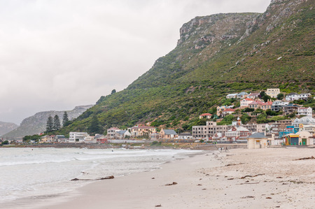 hill station tree: CAPE TOWN, SOUTH AFRICA - DECEMBER 12, 2014:  Unidentified surfers at Muizenberg beach on a gloomy and rainy daybreak