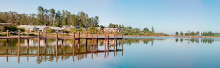 sir: CAPE TOWN, SOUTH AFRICA - DECEMBER 18, 2014: Early morning panorama of houses next to a dam with jetty on the Wedderville Estate near Sir Lowrys Pass