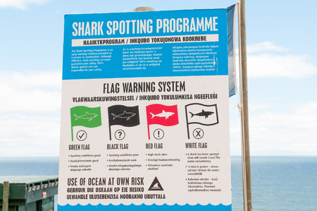 els: ROOI ELS SOUTH AFRICA  DECEMBER 23 2014: Poster at a shark spotting point on Clarence Drive depicting the meaning of the different flags in the flag spotting program