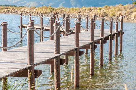 sir: Repeating pattern of wooden poles in a jetty in a dam near Sir Lowrys Pass