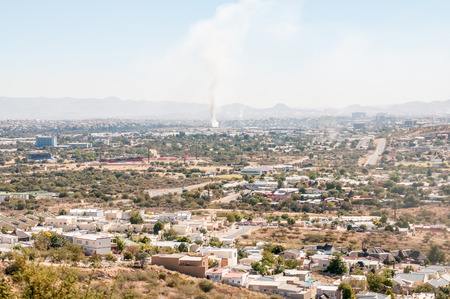 hazy: WINDHOEK, NAMIBIA - JUNE 9, 2012: A hazy view of Windhoek from the south with several veld fires and dust storms polluting the air.