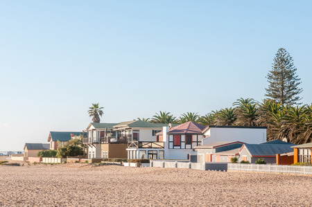 above 18: SWAKOPMUND, NAMIBIA - JUNE 18, 2012: A beach scene in Swakopmund with houses just above the high water mark