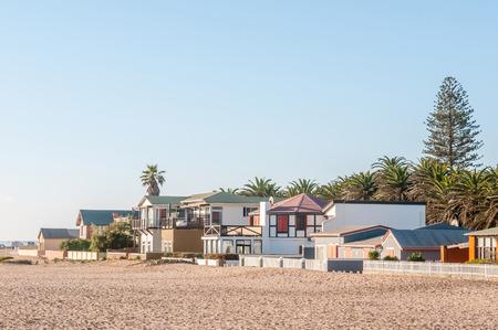 swakopmund: SWAKOPMUND, NAMIBIA - JUNE 18, 2012: A beach scene in Swakopmund with houses just above the high water mark