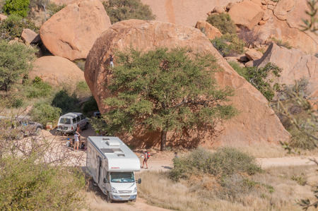 spitzkoppe: SPITZKOPPE, NAMIBIA - JUNE 5, 2011: Unidentified rock climbers scaling a huge boulder at a camp site at Spitzkoppe Editorial