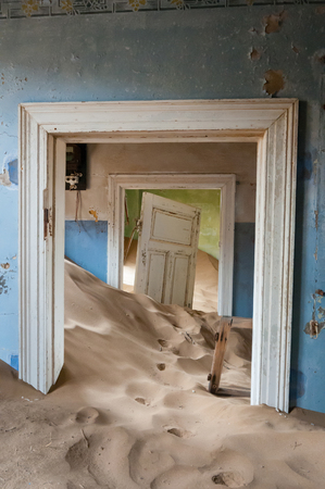 kolmanskop: Sand taking over an historic old building at the ghost town of Kolmanskop near Luderitz, Namibia.
