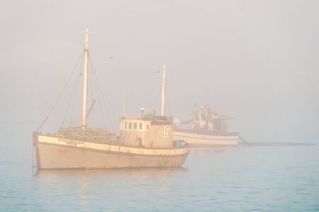 luderitz: LUDERITZ, NAMIBIA - JUNE 13, 2011: Fishing boats are visible through thick mist at the harbor in Luderitz
