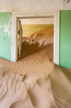 kolmanskop: Sand taking over an historic old building at the ghost town of Kolmanskop near Luderitz, Namibia.