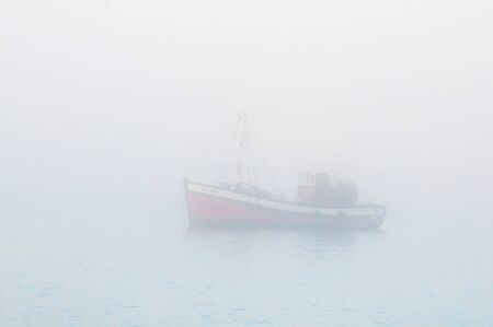 luderitz: LUDERITZ, NAMIBIA - JUNE 13, 2011: A fishing boat is barely visible through thick mist at the harbor in Luderitz