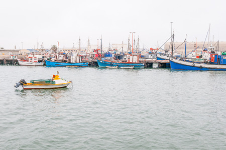 luderitz: LUDERITZ, NAMIBIA - JUNE 14, 2011: Fishing boats at the harbor in Luderitz on a gloomy day. The small town is known for its crayfish inustry Editorial