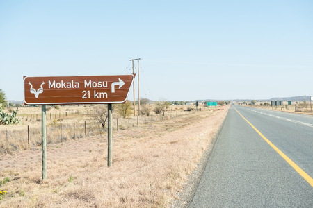 northern african: MODDERRIVIER, SOUTH AFRICA - AUGUST 9, 2015: Road sign next to the N12 road near Modderrivier giving directions to the Mosu Camp in the Mokala National Park in South Africa