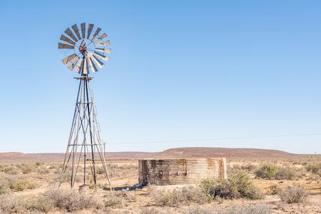 南アフリカ共和国 - 水漏れダムとウィンドミルのポンプ水の典型的な農村カルー シーン 写真素材