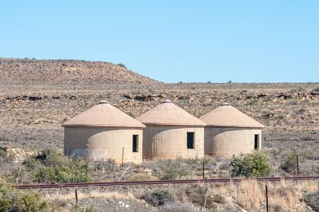 northern african: Three unoccupied railway worker rondavels next to the inoperative railway line between Carnavon and Williston in the arid Northern Cape Karoo region of South Africa