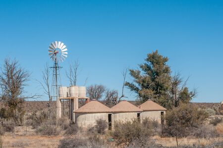 northern african: Three unoccupied rondavels next to a windpump and water storage tanks between Carnavon and Williston in the arid Northern Cape Karoo region of South Africa Stock Photo