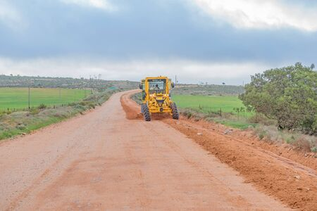 grader: NUWERUS, SOUTH AFRICA - AUGUST 13, 2015: A road grader working on the road between Lutzville and Nuwerus