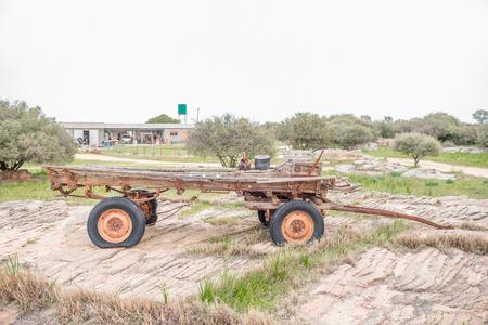 carreta madera: Nieuwoudtville, Sudáfrica - 11 de agosto 2015: Un histórico vagón de madera de edad en Groenrivier granja después de la puesta del sol.