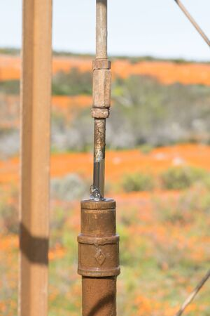 watertight: Water leaking at the watertight seal where the pull rod also called a pump rod of a water pumping windmill enters the drop pipe