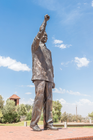 nelson mandela: BLOEMFONTEIN, SOUTH AFRICA, DECEMBER 21, 2015: The 6.5m bronze statue of Nelson Mandela on Naval hill in Bloemfontein with part of the historic powder magazine visible in the back