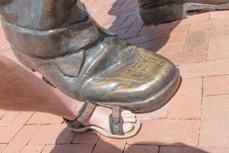 BLOEMFONTEIN, SOUTH AFRICA, DECEMBER 21, 2015: A foot of the 6.5m bronze statue of Nelson Mandela on Naval hill in Bloemfontein compared to a normal foot