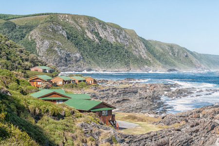 chalets: STORMS RIVER MOUTH, SOUTH AFRICA - FEBRUARY 28, 2016:  The restaurant, chalets and the day visitor picnic site at Storms River Mouth. A viewpoint is visible on top of the mountain