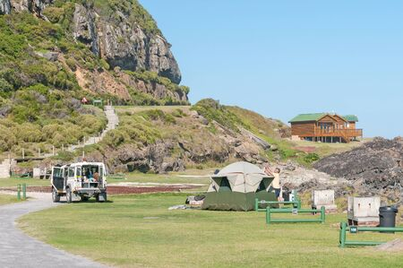 chalets: STORMS RIVER MOUTH, SOUTH AFRICA - FEBRUARY 28, 2016:  Tourists erecting a tent, with chalets in the back, at the rest camp at Storms River Mouth